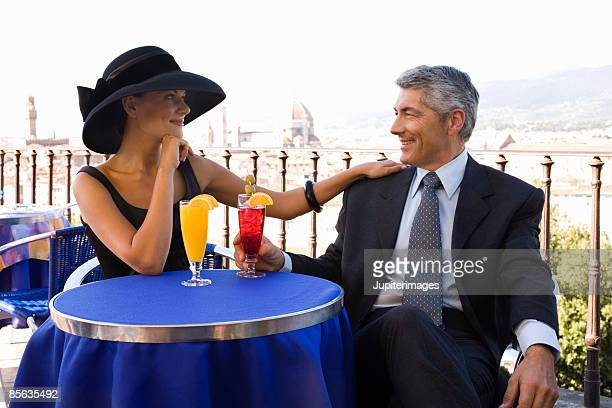 Elegant couple with drinks outdoors, Florence, Italy