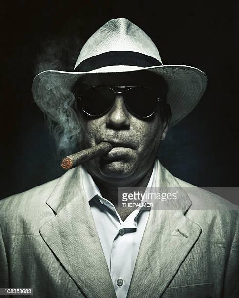Elegante kubanische geheimnisvolle Mann Rauchen Sie eine Zigarre