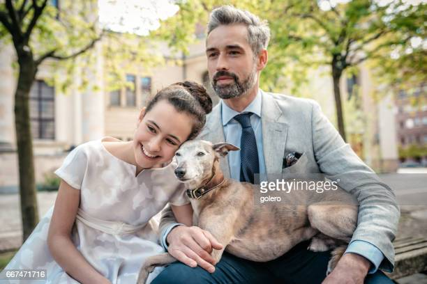 elegant father sitting on bench with well dressed daughter and dog