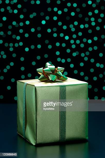 Elegant gift box with gold ribbon against green illumination background