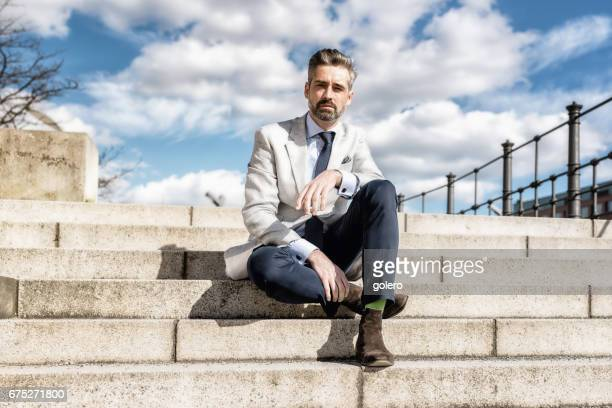 elegant handsome bearded businessman sitting on stairs outdoors