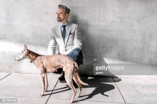 elegant handsome bearded businessman sitting with dog in front of concrete wall - building feature stock pictures, royalty-free photos & images