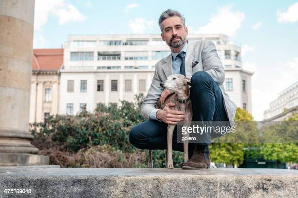 elegant handsome bearded businessman sitting with dog on wall in Berlin