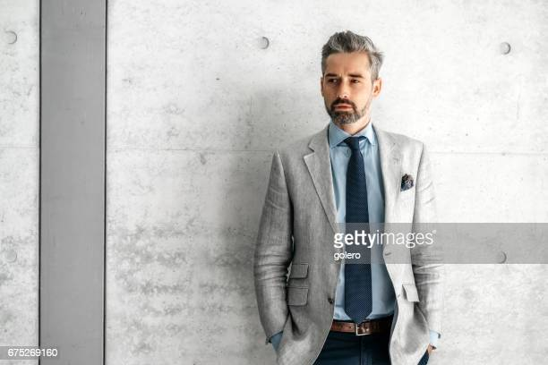 elegant handsome bearded businessman standing in front of concrete wall