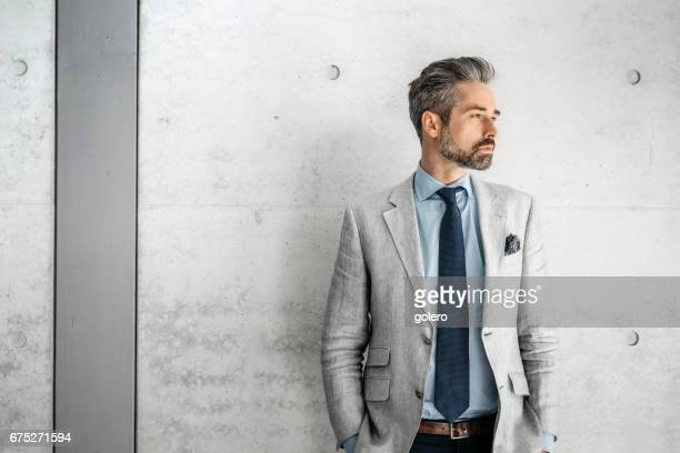 elegant handsome bearded businessman standing with dog  in business district - giacca foto e immagini stock
