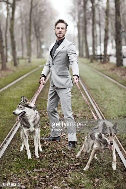 Élégant bel homme avec chien pack sur une voie ferrée