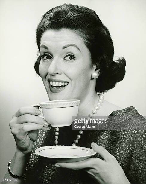 Elegant holding cup and saucer, (B&W), (Portrait)