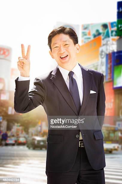 エレガントな日本の実業家で、peace サイン日本東京渋谷スクランブル交差点