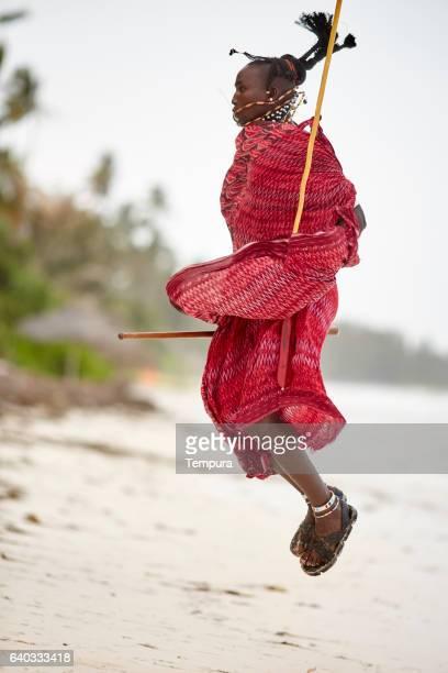 Elegant Maasai man jumping in Zanzibar's beach.