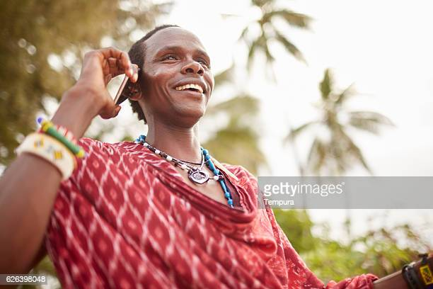 elegant maasai man using a smartphone. - warrior person stock photos and pictures