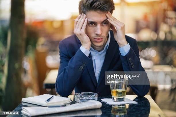 Elegant male smoking cigarette and feeling depressed