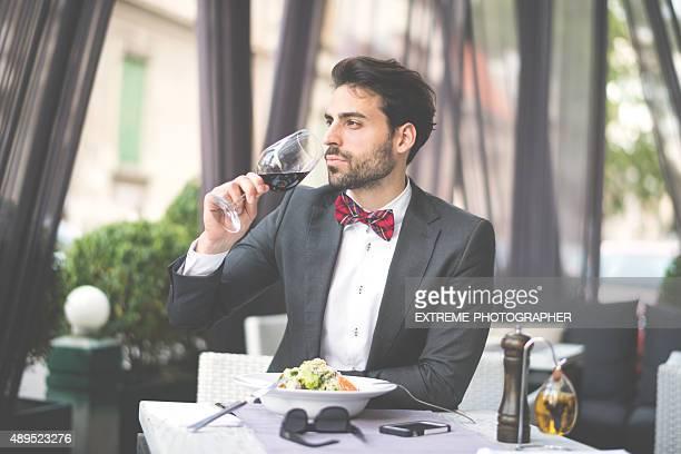 Élégant homme de boire du vin rouge