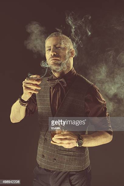 Elegant man drinking scotch whisky and smoking cigar