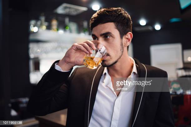 elegant man drinking whiskey in the bar - scotch whiskey stock pictures, royalty-free photos & images