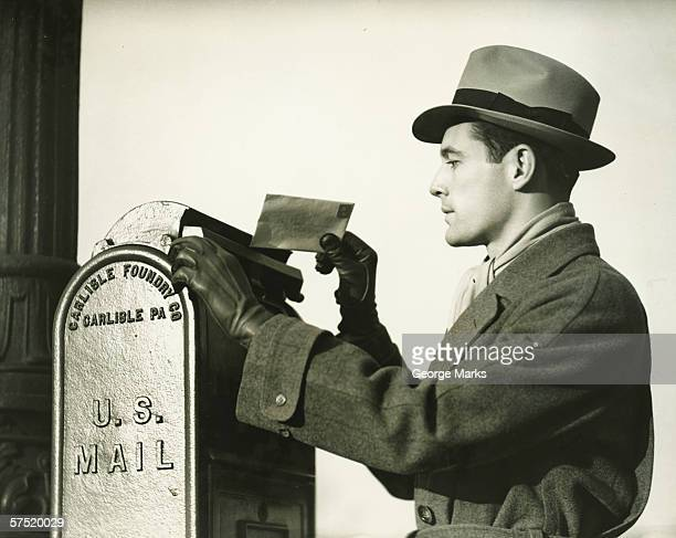 elegant man dropping letter into mailbox, (b&w) - fedora stock pictures, royalty-free photos & images