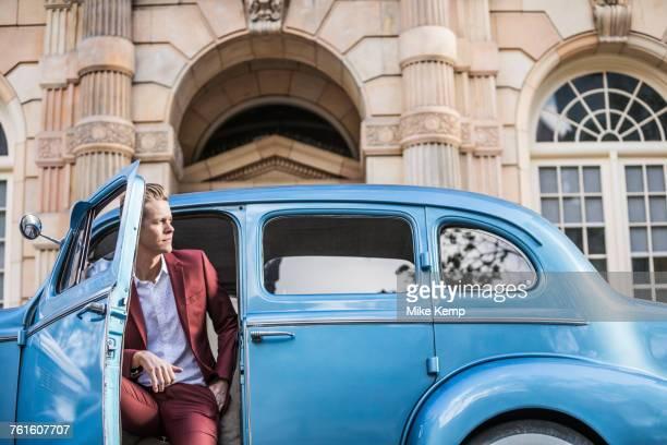 elegant man sitting in vintage car - ワインレッド ストックフォトと画像