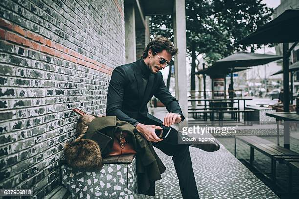 elegant man sitting on bench - accessoires stock-fotos und bilder