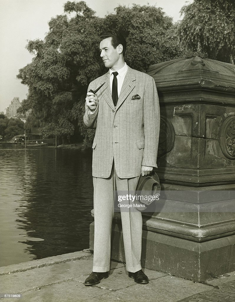 Elegant man smoking pipe by park lake, (B&W), portrait : Stock Photo