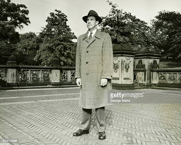 elegant man standing on courtyard, (b&w), (portrait) - overcoat stock pictures, royalty-free photos & images