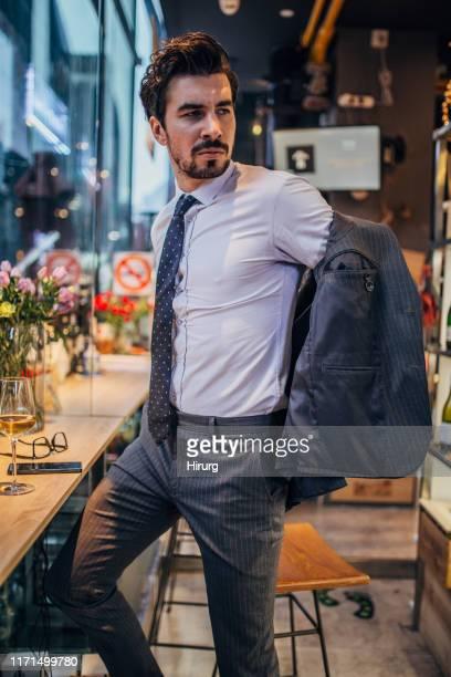 uomo elegante che si toglie la giacca - giacca da abito foto e immagini stock