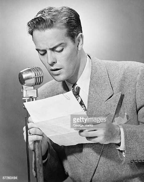 Elegant man talking into microphone in studio, (B&W)