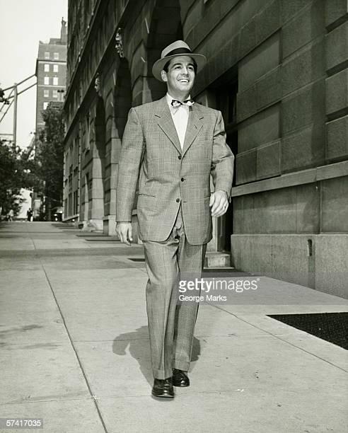 elegant man walking on sidewalk, (b&w) - fedora stock pictures, royalty-free photos & images