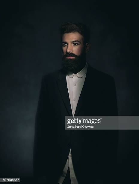 Elegant man with beard in make-up, looking away