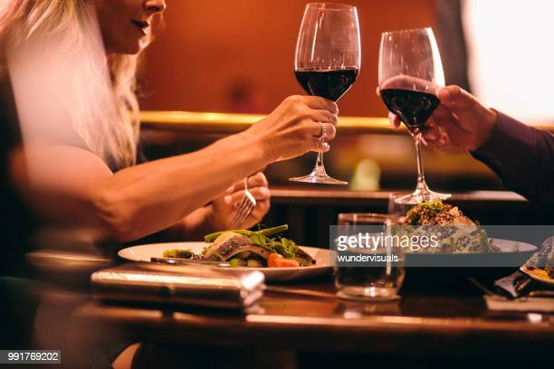 elegant mature couple dining and toasting with wine at restaurant - fish love stock photos and pictures