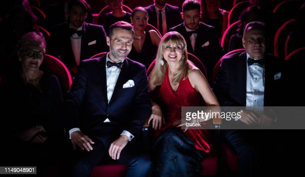 elegant mature couple watching movie in the cinema - formalwear stock pictures, royalty-free photos & images