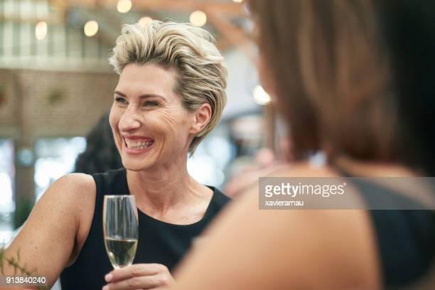 Elegant mature woman enjoying a drink after work