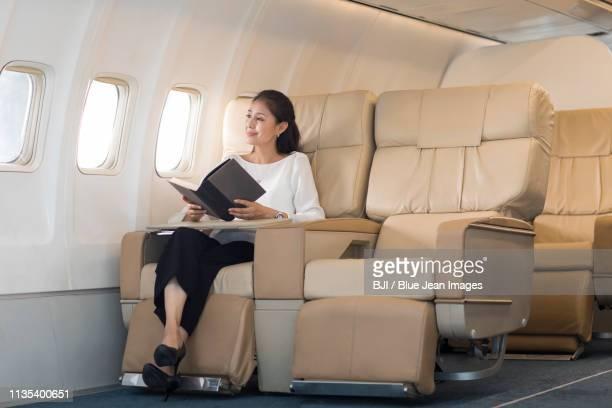 elegant mature woman reading book on airplane - 席 ストックフォトと画像