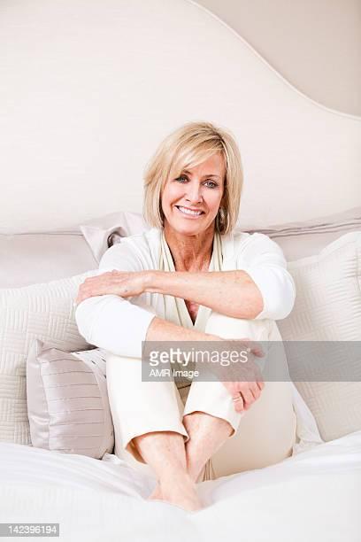 Elegante mujer madura sala de estar, con sus brazos y piernas cruzadas