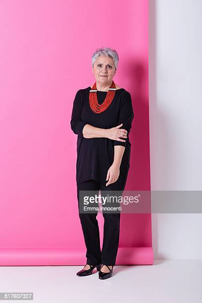elegant mature woman, studio shot in pink