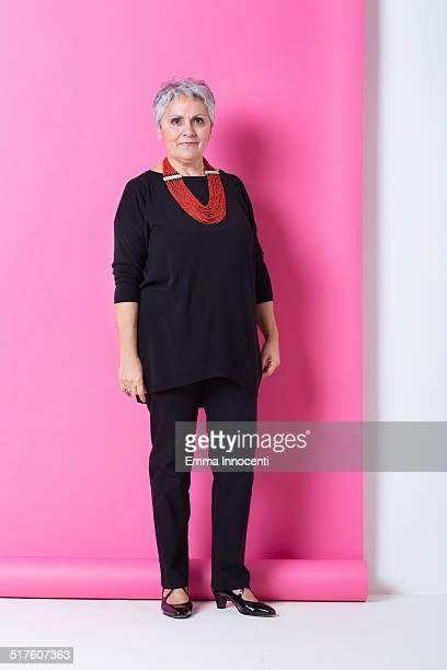 elegant mature woman, studio shot in pink