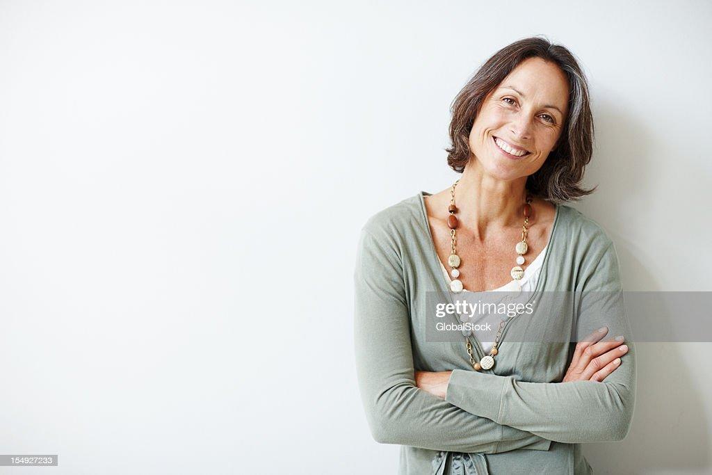 Elegante meio envelhecido mulher com os braços cruzados contra branco : Foto de stock