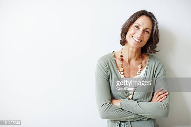 elegant middle aged woman with her arms crossed against white - glimlachen stockfoto's en -beelden