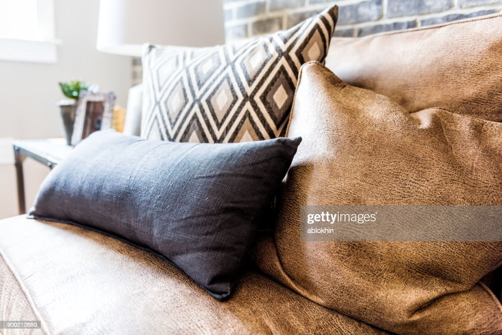 Elegant modern room closeup of leather couch and pillows in staging model house, home or apartment : Stock Photo