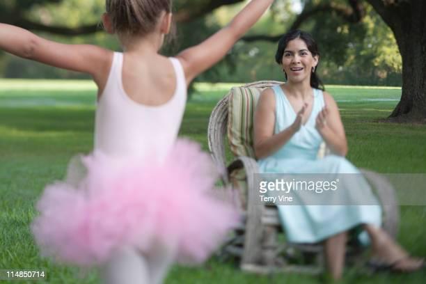 Elegant mother sitting in backyard with ballerina daughter