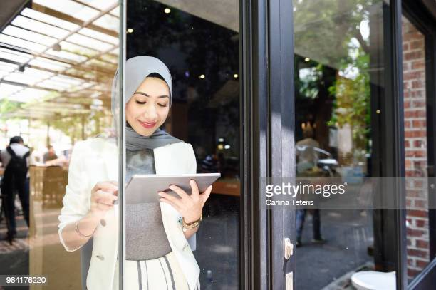 elegant muslim business woman working on a tablet through glass - malaysian culture stock pictures, royalty-free photos & images