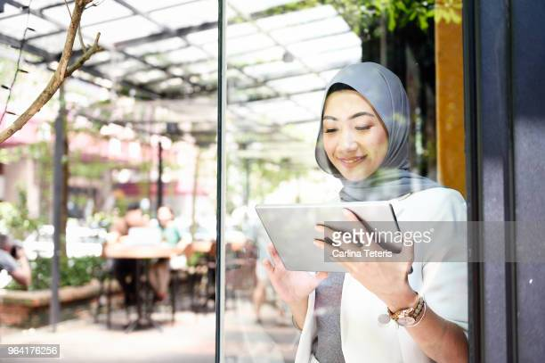 elegant muslim business woman working on a tablet through glass - islam fotografías e imágenes de stock