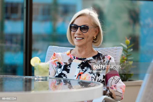 elegant old lady drinking a caipirinha - confortável stock photos and pictures