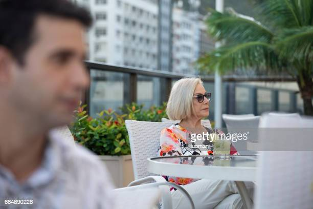 elegant old lady drinking a caipirinha - terceira idade stock photos and pictures