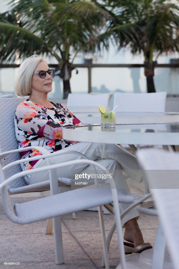 Elegant old lady drinking a caipirinha : Stock Photo