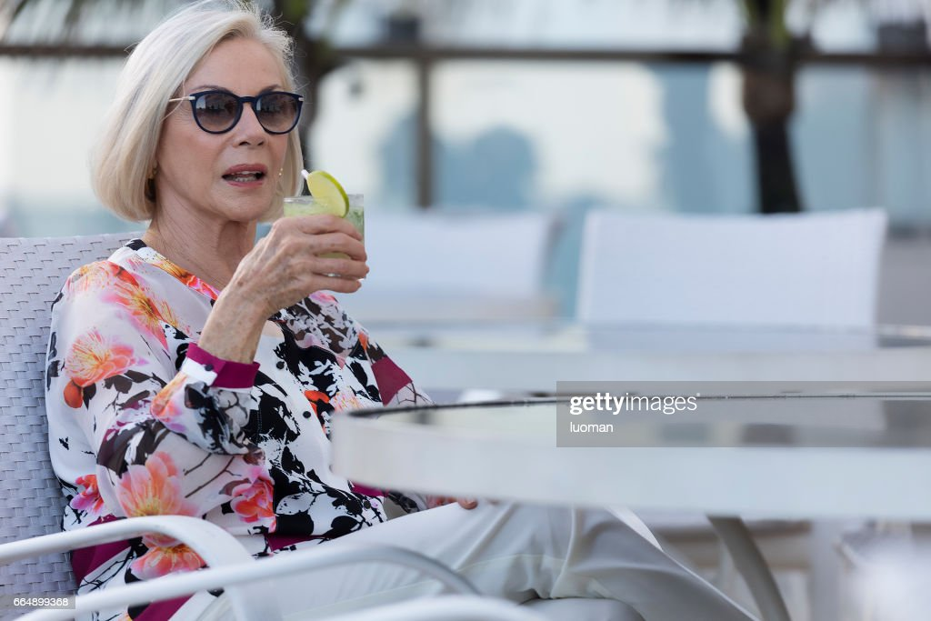 Elegant old lady drinking a caipirinha : Stock Photo