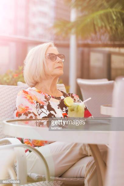Elegant old lady drinking a caipirinha