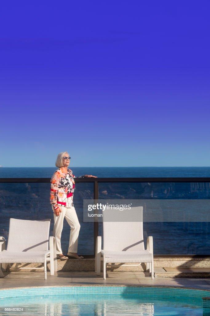 Elegant old lady near the swimmimg pool : Stock Photo