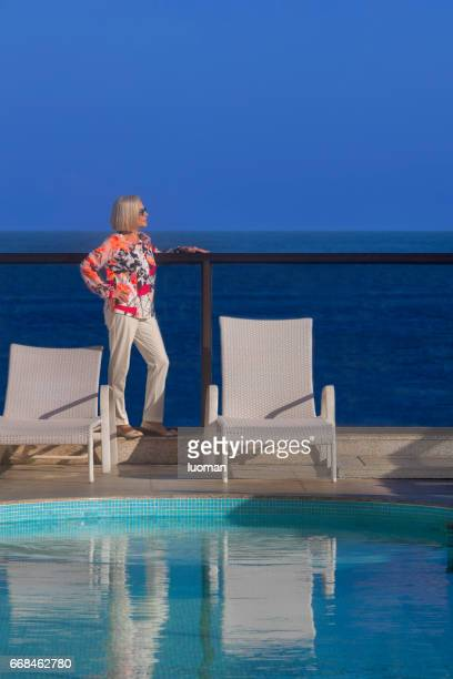 elegant old lady near the swimmimg pool - terceira idade stock photos and pictures