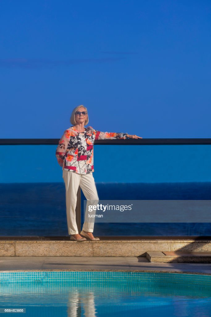 Elegant old lady near the swimmimg pool : Stock Photo