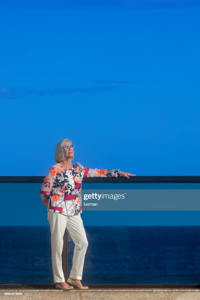 Elegant old lady outside in front of the sea : Stock Photo