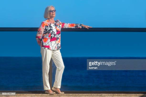 elegant old lady outside in front of the sea - terceira idade stock photos and pictures